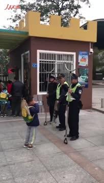 开学日茶山一小孩向门口护学民警敬礼后转身微笑跟妈妈挥手说再见
