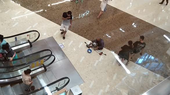 流浪大爷拄双拐进商场避暑 席地而坐摆碗讨钱
