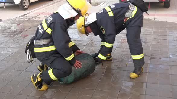 """厨房煤气罐起火  消防员手拎""""火罐""""转移安全区域"""