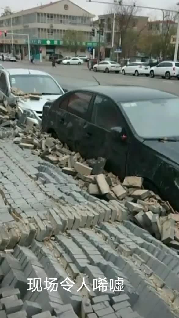 大风刮倒建筑围墙 众多小车被砸