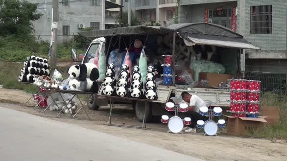 小伙在公路旁卖仿真大熊猫,吸引不少路过司机观望